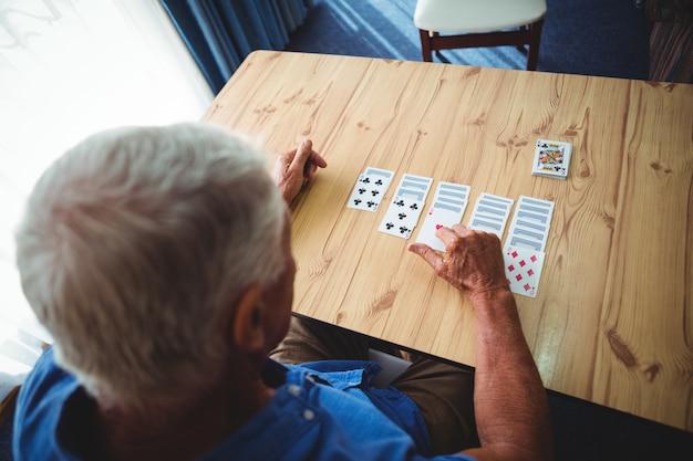 Älterer mann, der karten auf einem tisch spielt