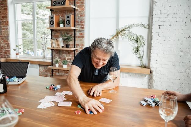Älterer mann, der karten spielt und wein mit freunden trinkt, sieht glücklich aus