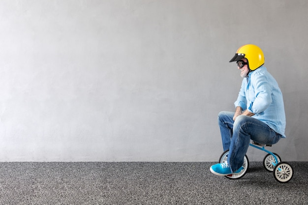 Älterer mann, der kinderfahrrad reitet. porträt des lustigen geschäftsmannes in voller länge gegen betonwand mit kopienraum. unternehmensgründungskonzept