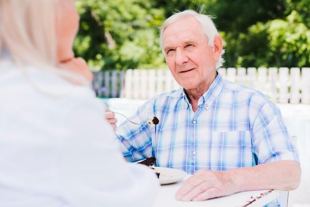Älterer mann, der kuchen auf äußerer veranda isst