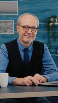 Älterer mann, der lächelnd in die kamera schaut, sitzt am arbeitsplatz am schreibtisch