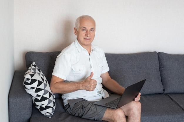 Älterer mann, der lächelt und daumen oben zeigt, während er am arbeitsplatz zu hause sitzt