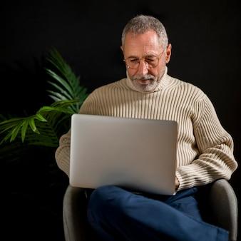 Älterer mann, der laptop im lehnsessel verwendet