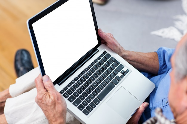 Älterer mann, der laptop im wohnzimmer verwendet