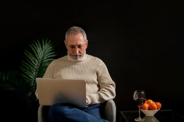 Älterer mann, der laptop nahe tangerinen und wein durchstöbert