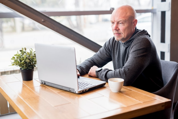 Älterer mann, der laptop verwendet