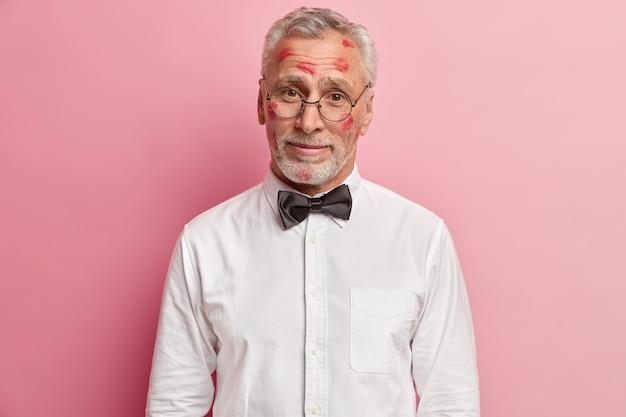 Älterer mann, der lippenstiftflecken auf gesicht hat