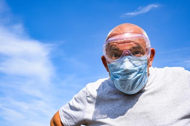 Älterer mann, der medizinische maske und schutzbrille trägt, die die kamera nahaufnahme auf einem blauen himmel mit wolken betrachten. coronavirus-konzept. atemschutz