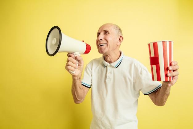 Älterer mann, der megaphon benutzt und gestreiftes paket hält