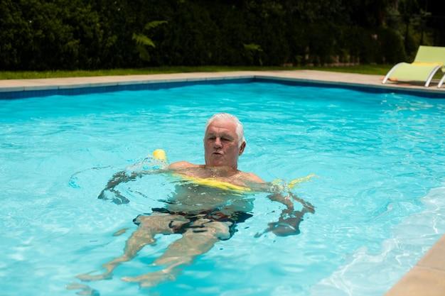 Älterer mann, der mit aufblasbarem schlauch im pool schwimmt