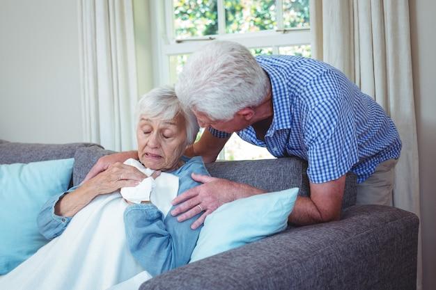 Älterer mann, der mit der kranken frau sitzt auf sofa spricht