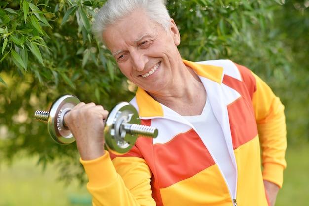 Älterer mann, der mit hantel im park trainiert