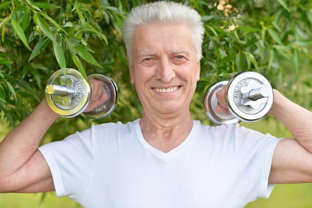 Älterer mann, der mit hanteln im park trainiert
