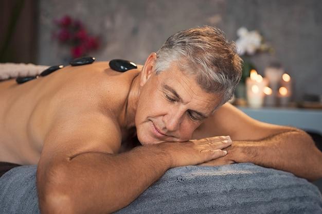 Älterer mann, der mit heißer steinmassage ruht