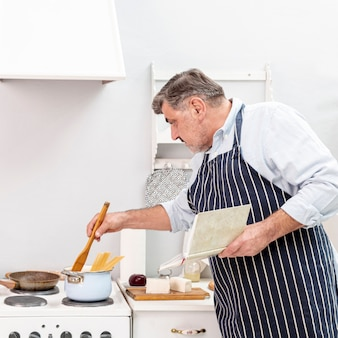 Älterer mann, der mit hölzernem löffel kocht