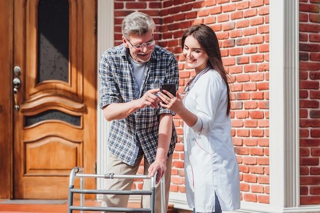 Älterer mann, der mit ihm kinder am telefon spricht, in der nähe des pflegeheims