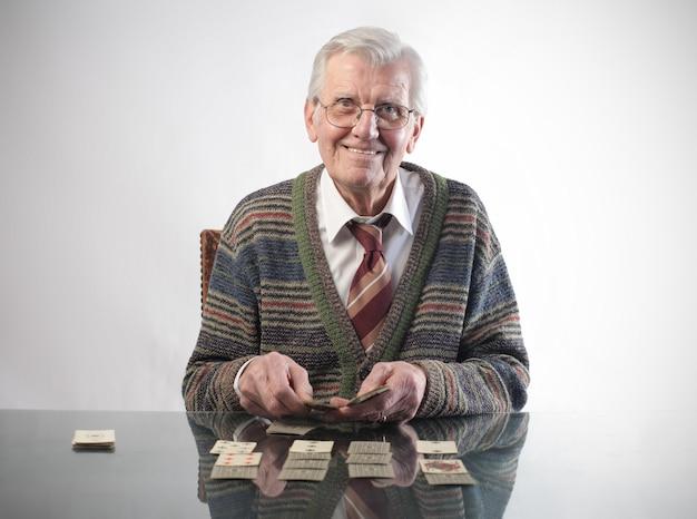 Älterer mann, der mit karten spielt