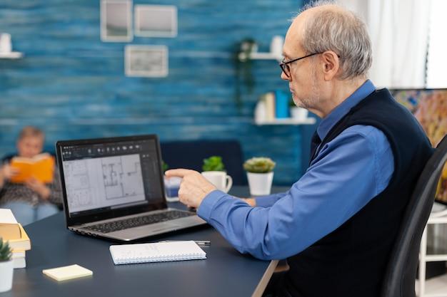 Älterer mann, der mit laptop arbeitet, um hausplan zu machen