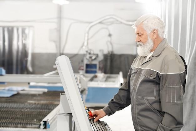 Älterer mann, der mit laserschneidmaschine auf fabrik arbeitet.