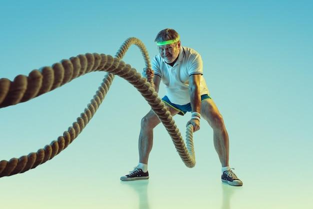 Älterer mann, der mit seilen auf gradientenhintergrund im neonlicht trainiert. das kaukasische männliche model in guter form bleibt aktiv und sportlich.