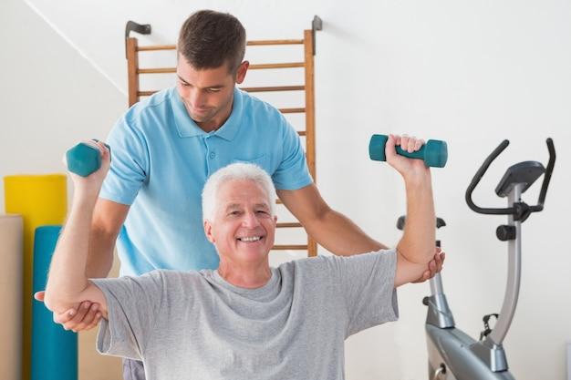 Älterer mann, der mit seinem trainer ausarbeitet