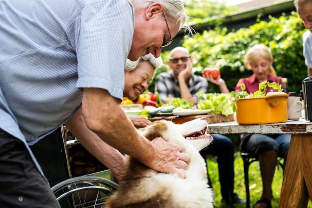 Älterer mann, der mit sibirischem huskey spielt