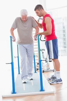 Älterer mann, der mit trainerhilfe geht