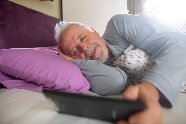 Älterer mann, der morgens die nachrichten auf dem tablett im bett überprüft
