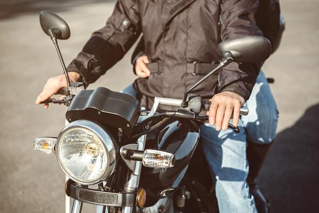 Älterer mann, der motorrad auf der straße steuert