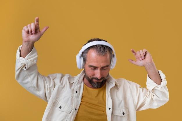 Älterer mann, der musik über kopfhörer hört