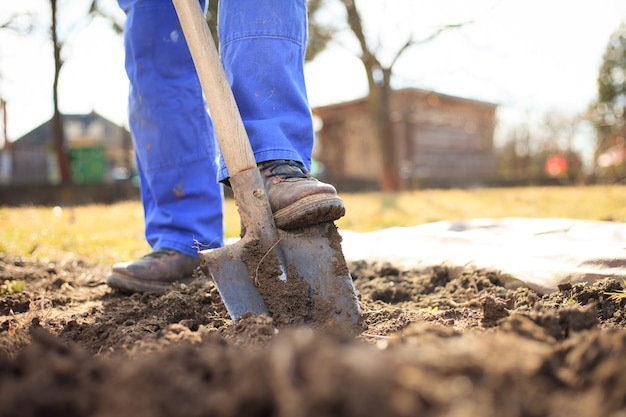 Älterer mann, der nach dem winter einen garten für neue pflanzen gräbt