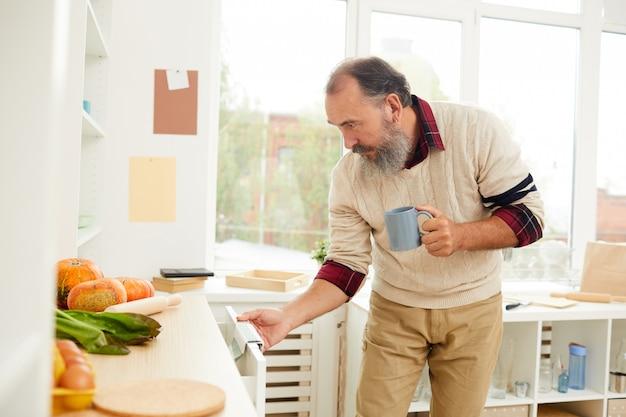Älterer mann, der nach nahrung in der küche sucht