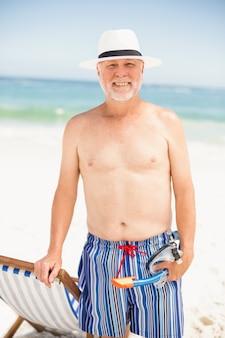 Älterer mann, der nahe bei sonnenstuhl steht