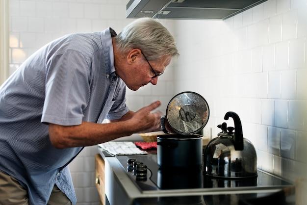 Älterer mann, der nahrungsmittelküche kocht
