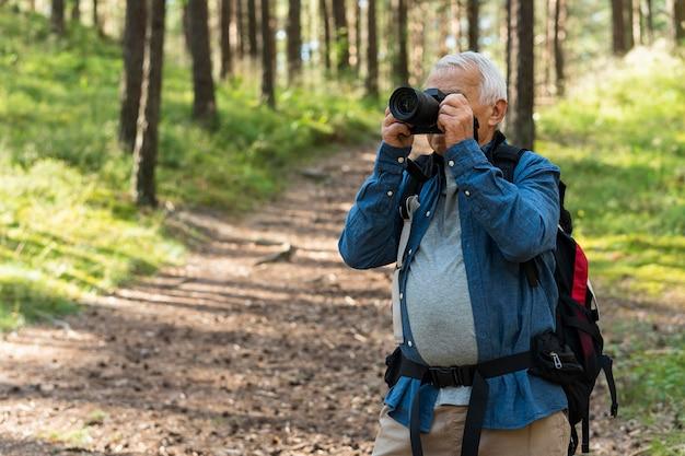 Älterer mann, der natur mit kamera erforscht
