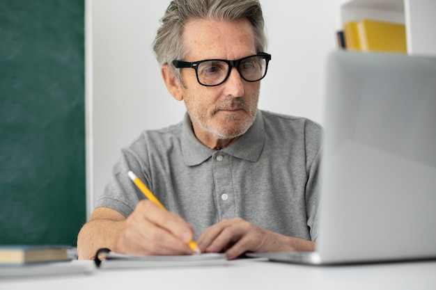 Älterer mann, der online-kurse auf einem laptop macht