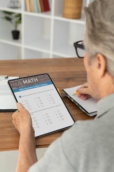 Älterer mann, der online-kurse auf einem tablet macht