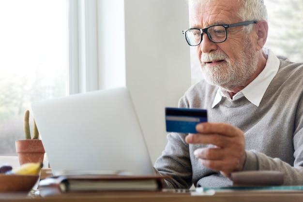 Älterer mann, der online mit einer kreditkarte kauft
