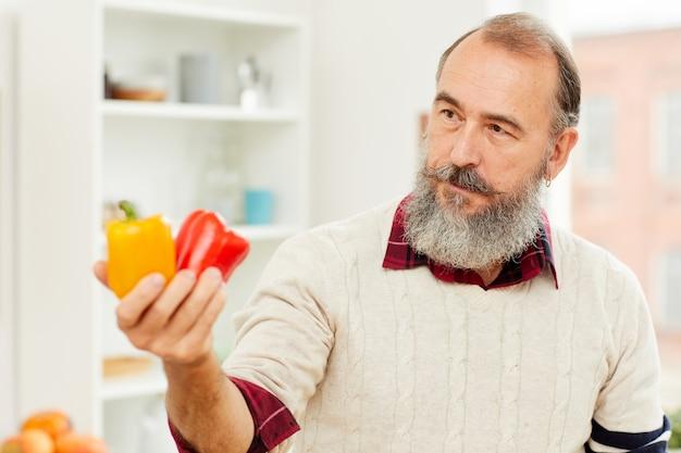 Älterer mann, der paprika hält