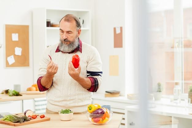 Älterer mann, der paprika wählt