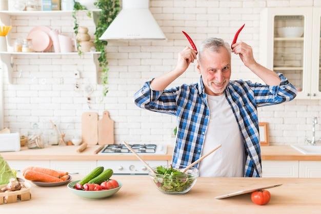 Älterer mann, der pfeffer des roten paprikas nahe dem kopf als hörner des roten teufels in der küche hält