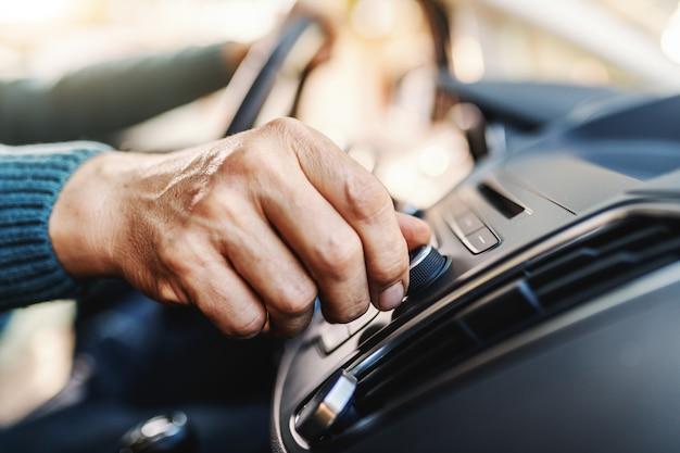 Älterer mann, der radiosender wechselt, während er in seinem auto sitzt.