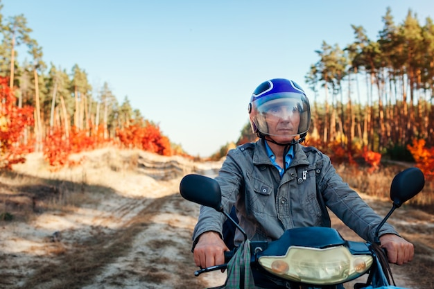 Älterer mann, der roller auf herbstwaldstraße reitet. fahrer im helm, der moped reitet. aktiver lebensstil