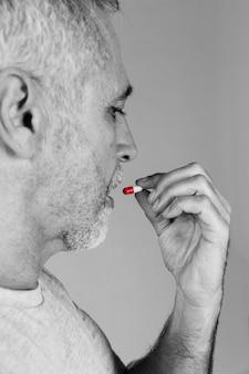 Älterer mann, der rote und weiße kapsel nimmt