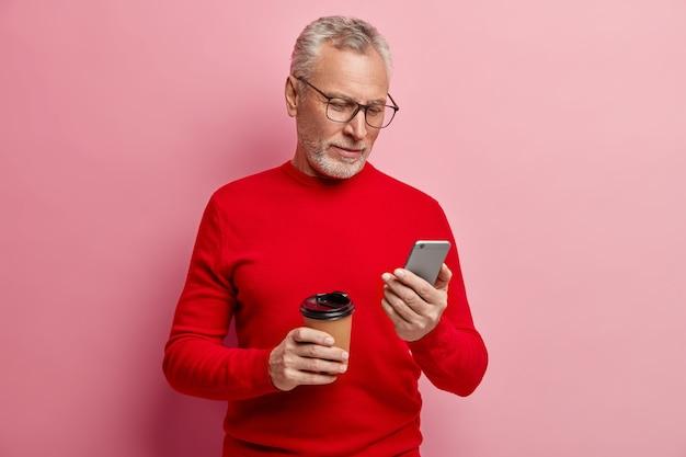 Älterer mann, der roten pullover und trendige brillen trägt