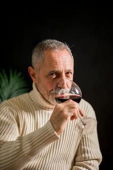 Älterer mann, der rotwein trinkt
