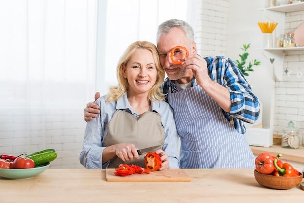 Älterer mann, der scheibe des roten pfeffers vor seinen augen in der küche hält