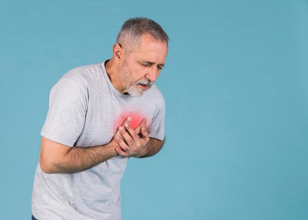 Älterer mann, der schmerz in der brust auf blauem hintergrund hat