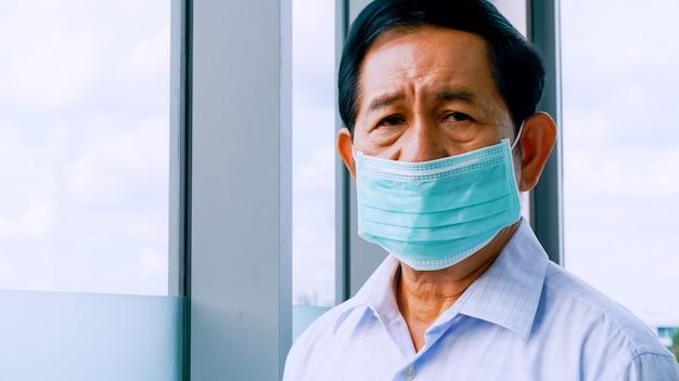 Älterer mann, der schützende gesichtsmasken während der quarantäne zu hause trägt.