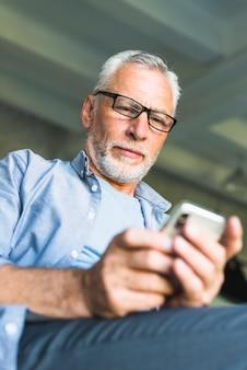 Älterer mann, der schwarze gläser unter verwendung des mobiltelefons trägt